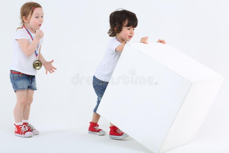 Petite fille avec la médaille sur le coffre admirant des regards au garçon photographie stock