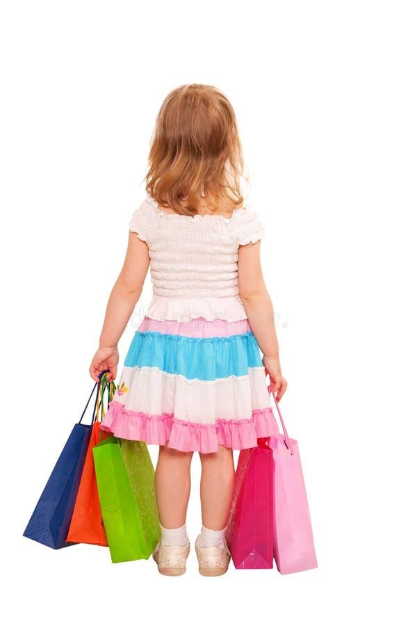 Petite fille avec la marche de sacs à provisions. Vue arrière. images stock
