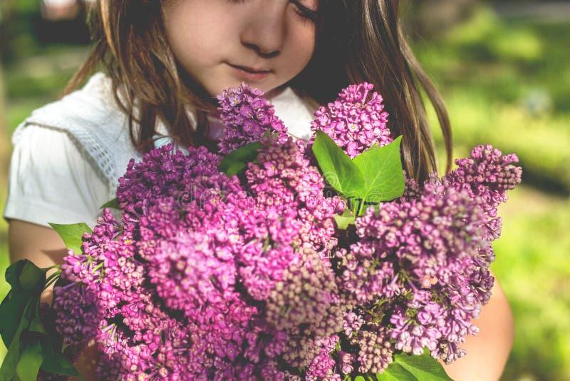 Petite fille avec le bouquet du lilas dans des ses mains image stock