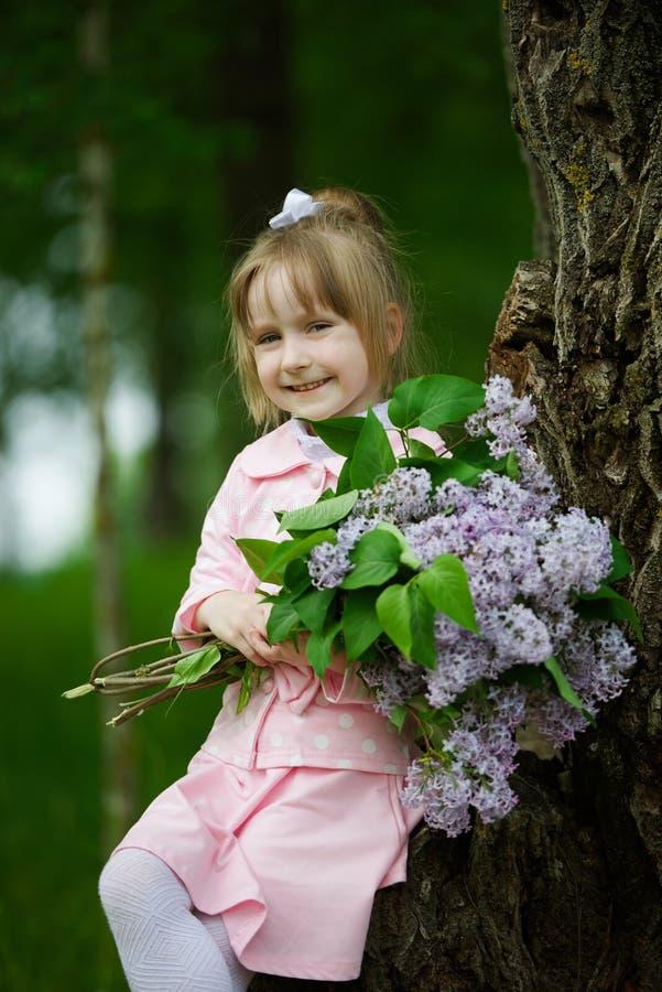 Petite fille avec le bouquet lilas images stock