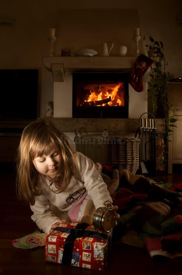 Petite fille avec le cadeau de Noël dans la chambre noire de nuit images stock