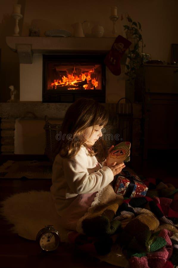 Petite fille avec le cadeau de Noël dans la chambre noire de nuit photo stock