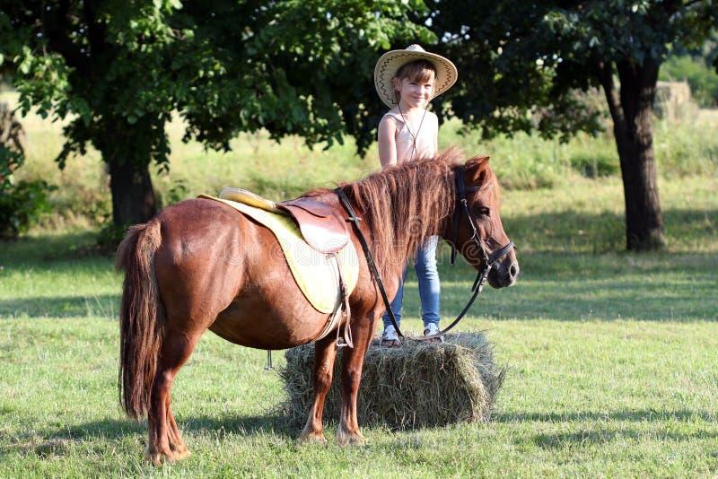 Petite fille avec le chapeau de cowboy et le cheval de poney images stock