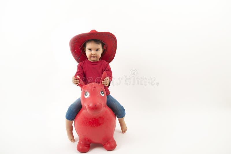 Petite fille avec le chapeau de cowboy rouge montant le cheval de jouet d'o photographie stock