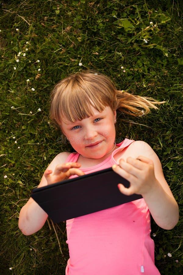Petite fille avec le comprimé photographie stock