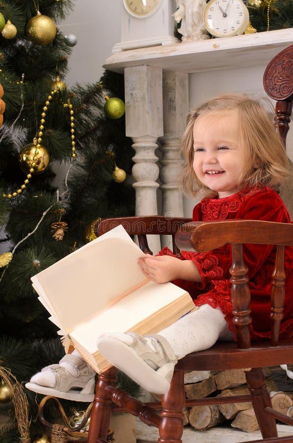 Petite fille avec le livre dans l'intérieur de Noël image libre de droits