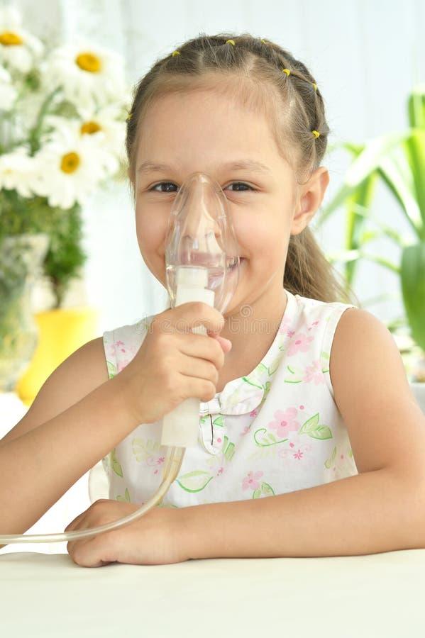 Petite fille avec le masque pour l'inhalation photos stock