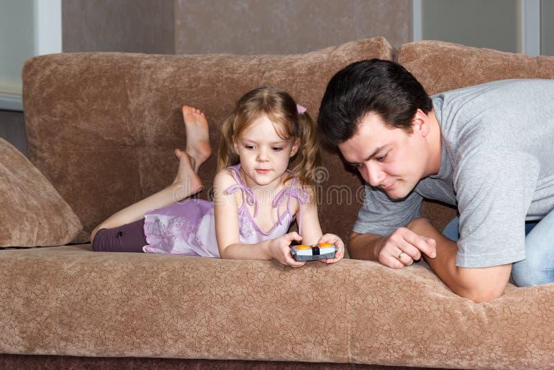 Petite fille avec le papa jouant sur le divan photos libres de droits