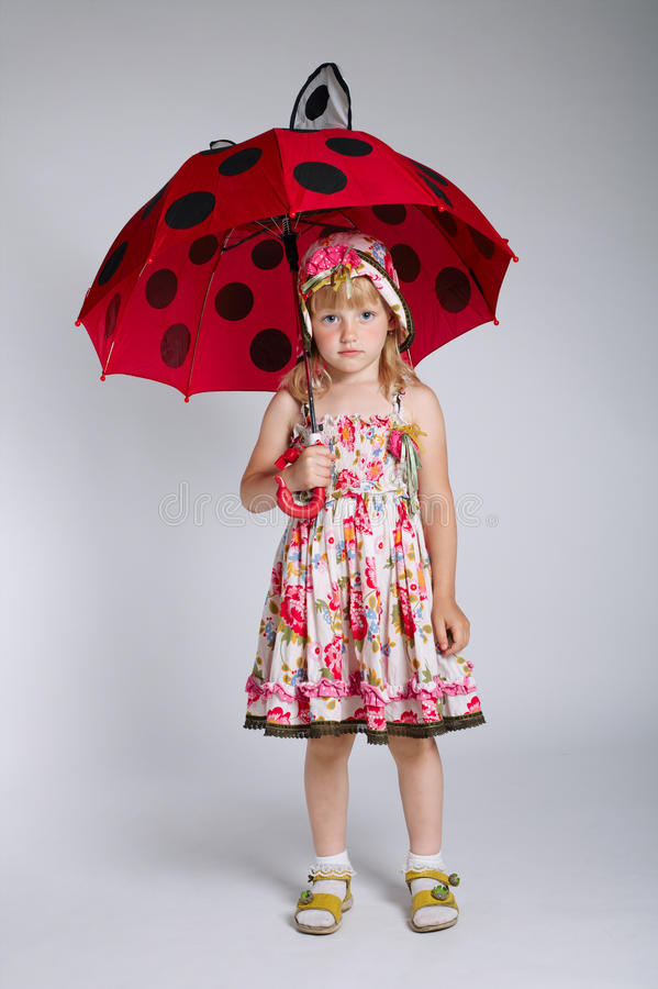 Petite fille avec le parapluie sur le blanc photo stock