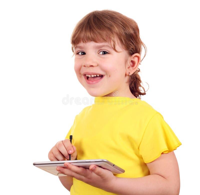 Petite fille avec le PC de tablette photographie stock