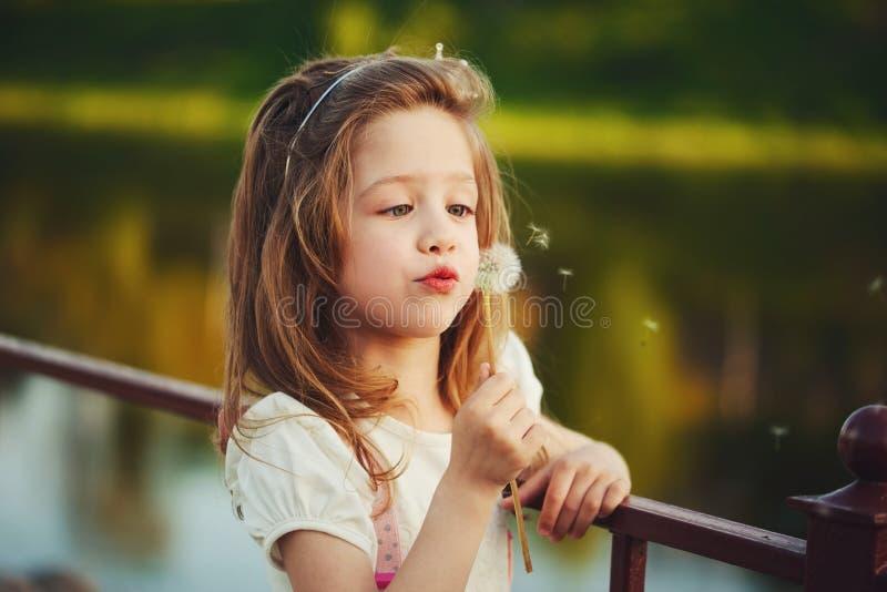 Petite fille avec le pissenlit en parc photo stock