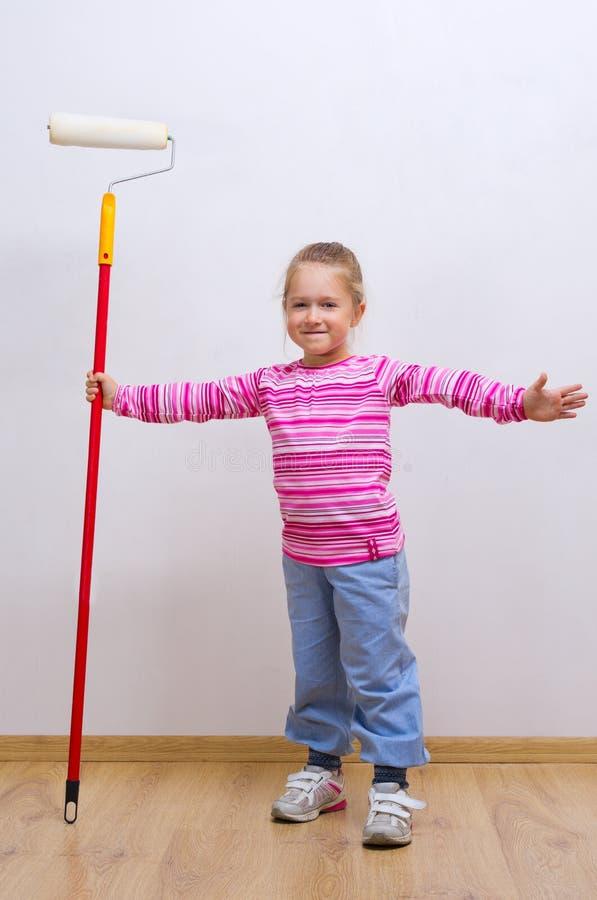 Petite fille avec le rouleau de peinture images stock