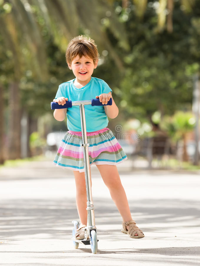 Petite fille avec le scooter images stock