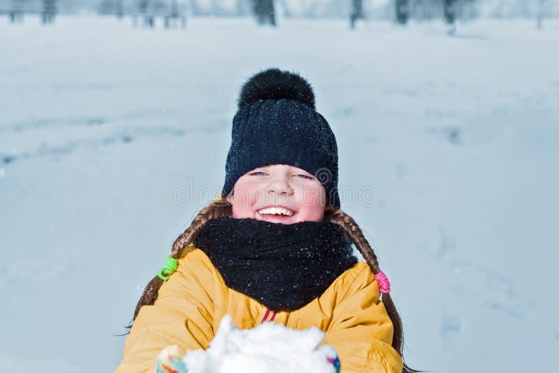 Petite fille avec le sourire de tresses enfant heureux donnant la neige portrait d'hiver d'enfant photo stock