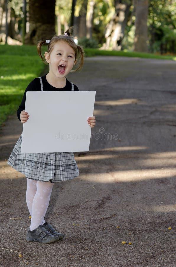 Petite fille avec le tableau blanc images stock
