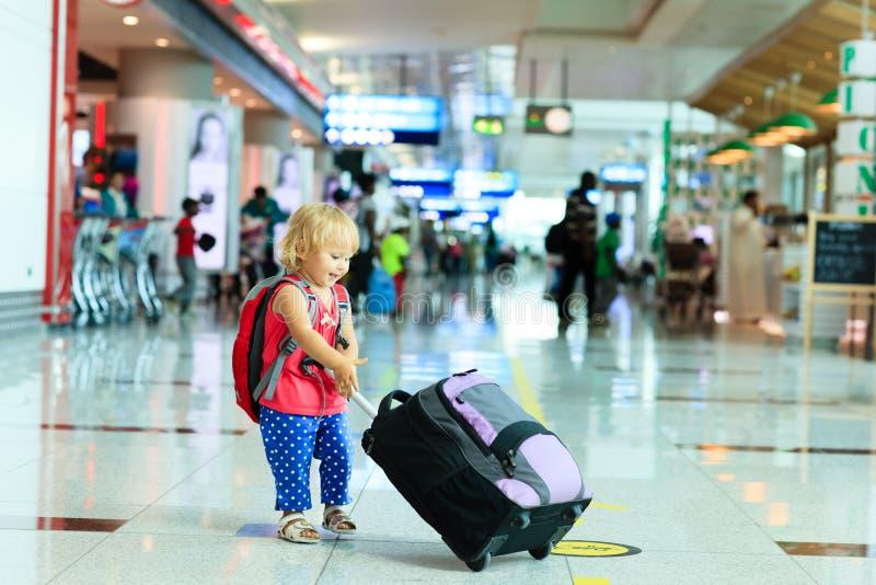 Petite fille avec le voyage de valise dans l'aéroport photographie stock libre de droits