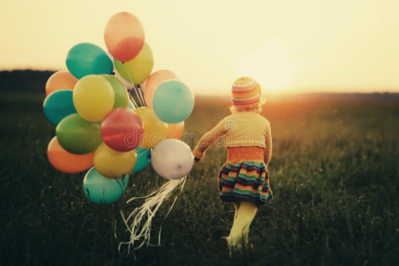 Petite fille avec les ballons colorés images libres de droits