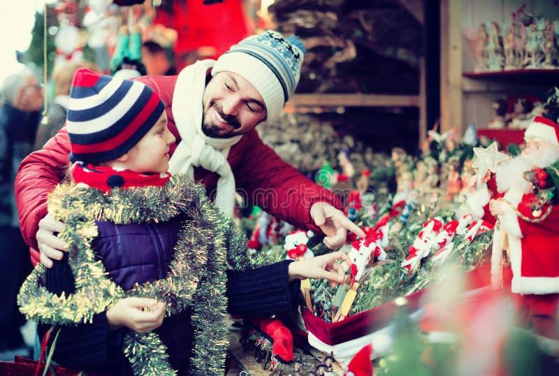 Petite fille avec les décorations de achat de papa pour Noël image stock