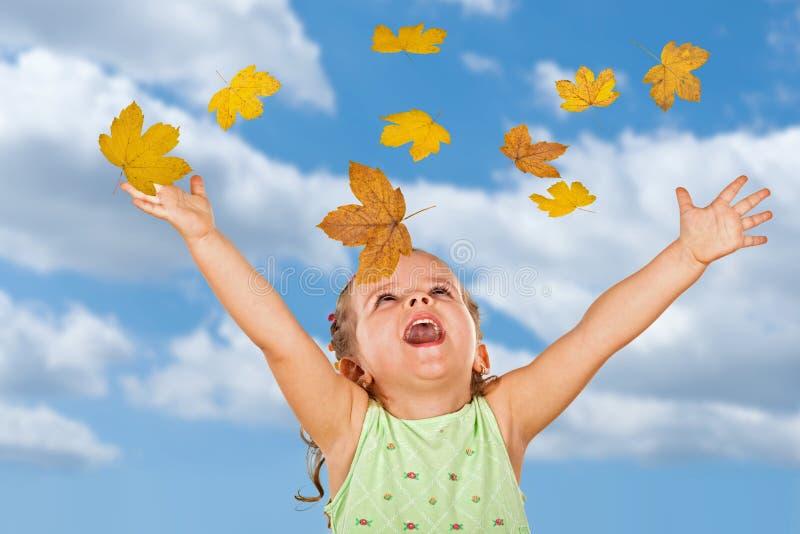Petite fille avec les lames d'automne en baisse photographie stock