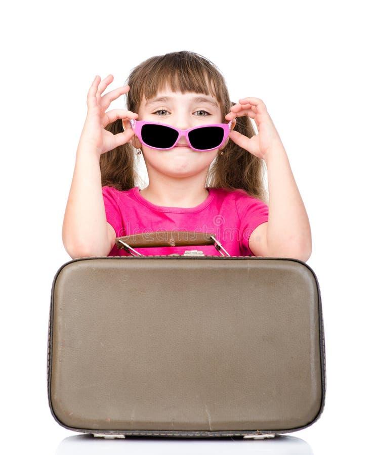 Petite fille avec les lunettes de soleil et la valise D'isolement sur le blanc image stock