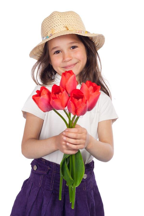 Petite fille avec les tulipes rouges images stock