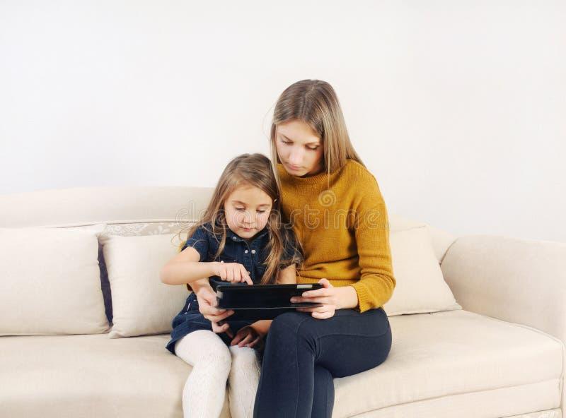 Petite fille avec sa mère à l'aide du dispositif de comprimé sur le sofa à h image stock