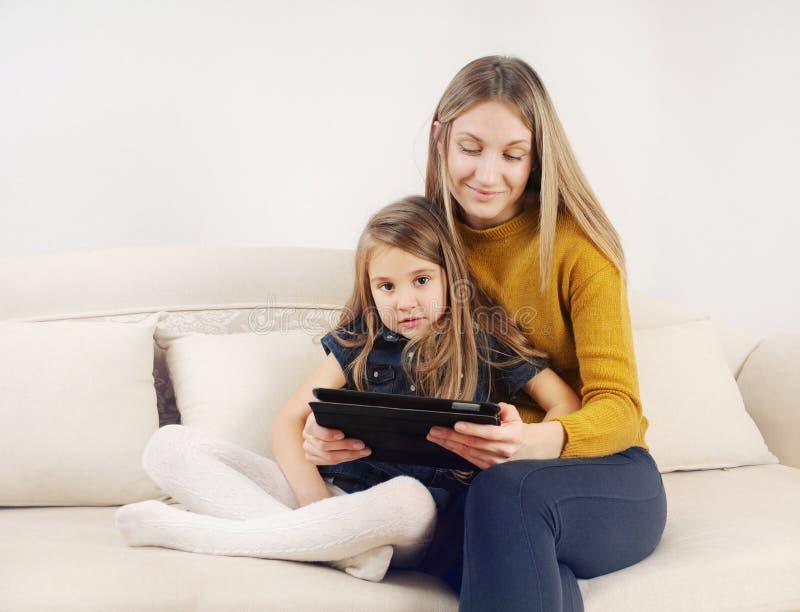 Petite fille avec sa mère à l'aide du dispositif de comprimé sur le sofa à h photo stock
