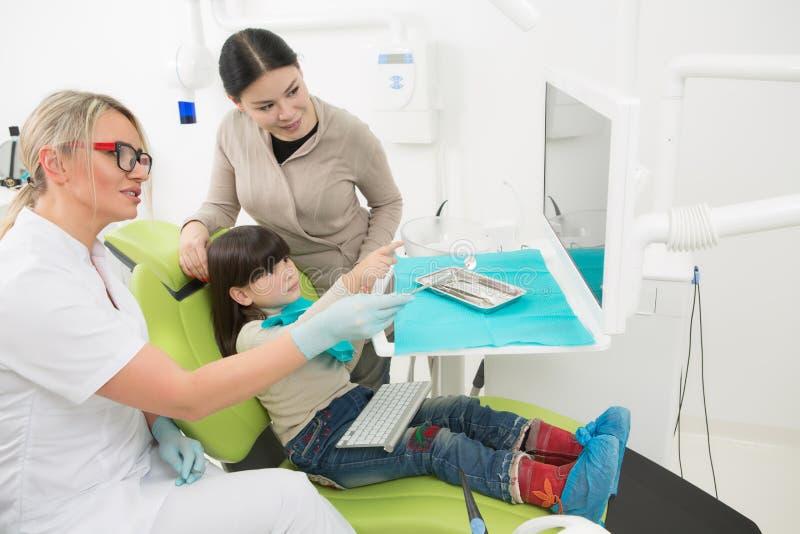 Petite fille avec sa mère au bureau du dentiste photo stock