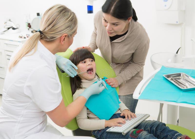 Petite fille avec sa mère au bureau du dentiste photos stock
