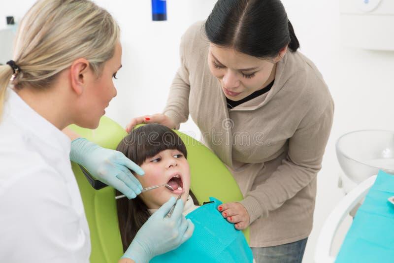 Petite fille avec sa mère au bureau du dentiste photographie stock libre de droits