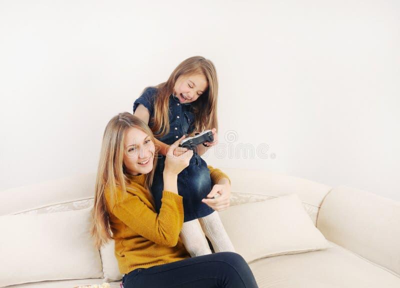 Petite fille avec sa mère jouant le dispositif de jeu vidéo de TV sur photos stock
