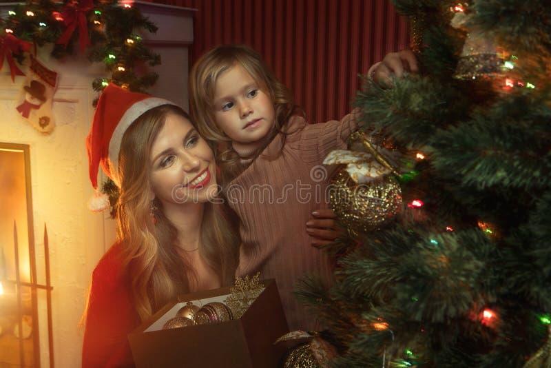 petite fille avec sa maman dans l'environnement de noël images stock