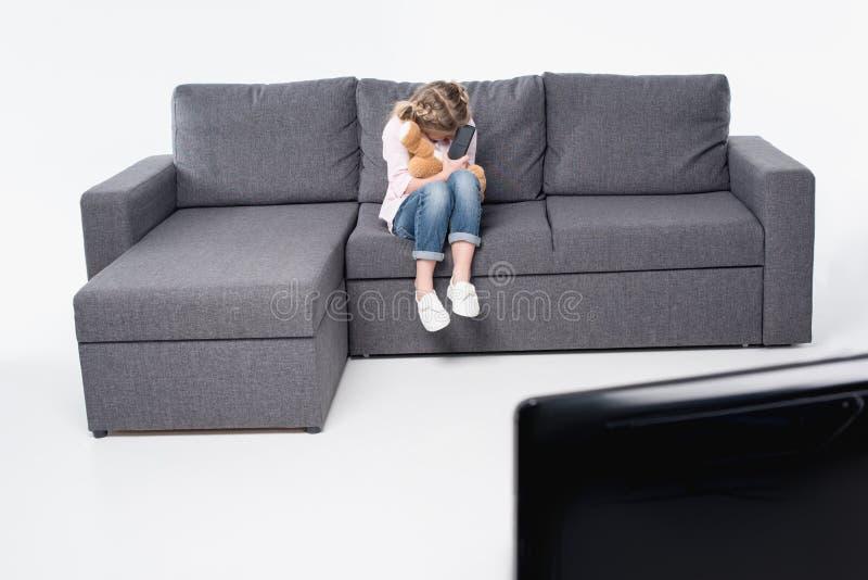 Petite fille avec sentiment d'ours de nounours effrayée tout en regardant la TV image libre de droits