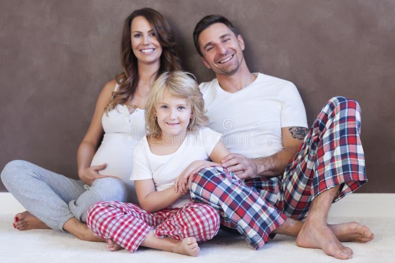 Petite fille avec ses parents à la maison image stock