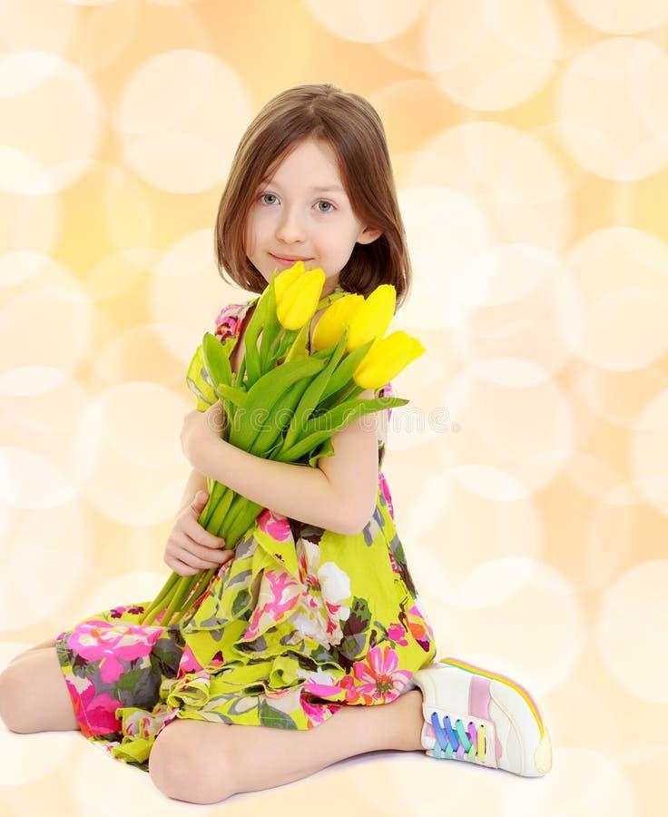 Petite fille avec un bouquet des tulipes jaunes photographie stock