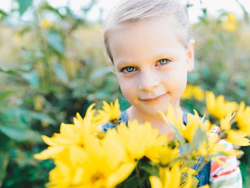 Petite fille avec un bouquet des wildflowers jaunes photographie stock libre de droits