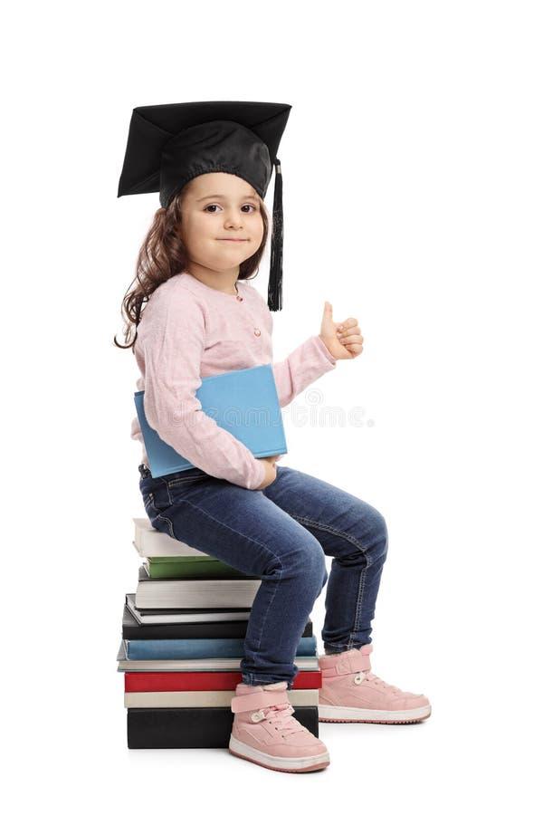 Petite fille avec un chapeau d'obtention du diplôme renonçant à un pouce photos stock