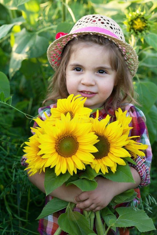 Petite fille avec un grand bouquet des tournesols photographie stock