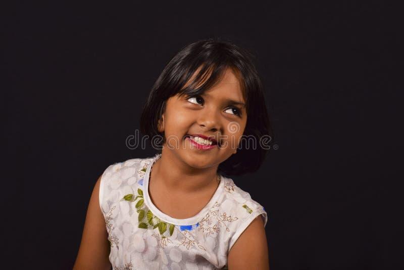 Petite fille avec un sourire mignon regardant l'appareil-photo contre un contexte noir images libres de droits