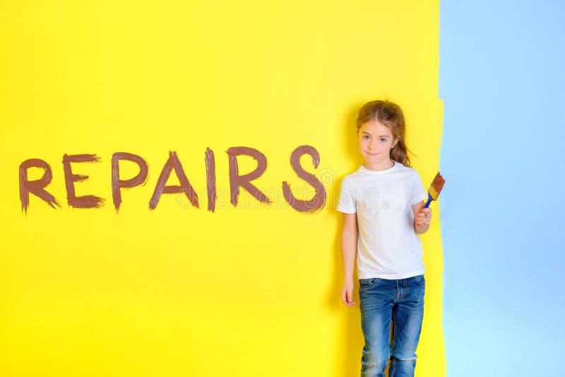Petite fille avec une brosse pour peindre dans des ses mains, supports près du mur peint photo libre de droits