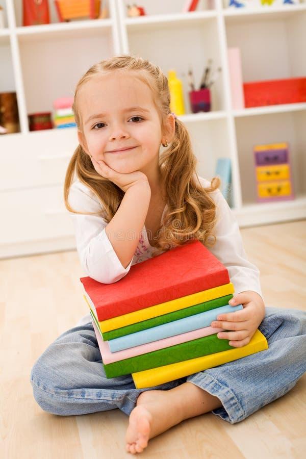 Petite fille avec une pile de livres photos stock