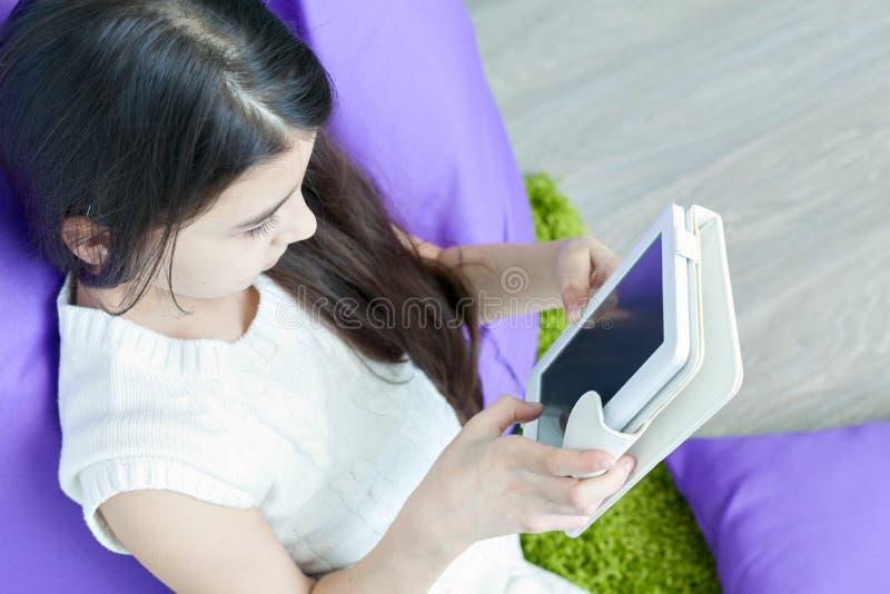 Petite fille avec une tablette à la maison photo libre de droits