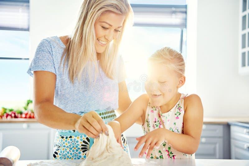 Petite fille ayant l'amusement aidant dans la cuisine photo libre de droits