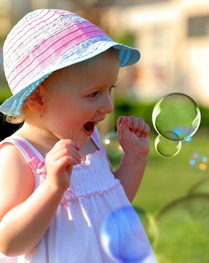 Petite fille ayant l'amusement avec des bulles de savon image libre de droits