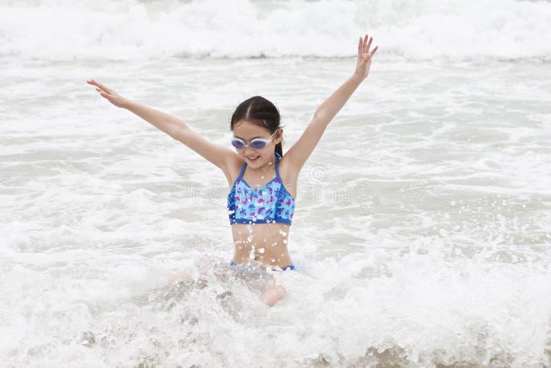 Petite fille ayant l'amusement en mer photographie stock