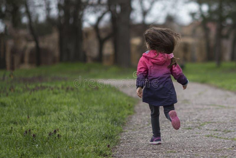 Petite fille ayant l'amusement, fonctionnant dans le parc photographie stock