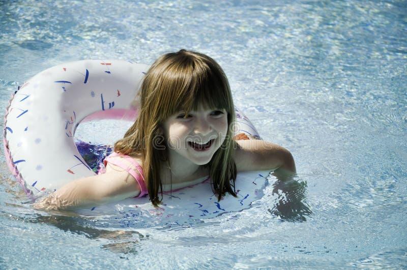 Petite fille ayant la natation d'amusement dans le regroupement photographie stock