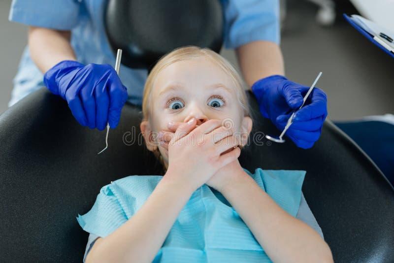 Petite fille ayant peur du contrôle aux dentistes image stock