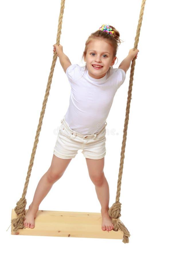 Petite fille balançant sur une oscillation photo libre de droits