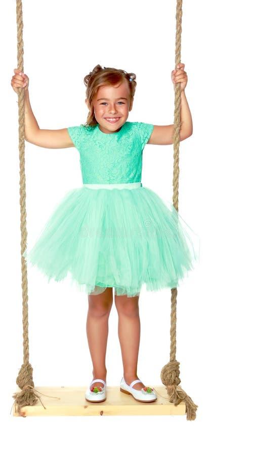 Petite fille balançant sur une oscillation photographie stock libre de droits